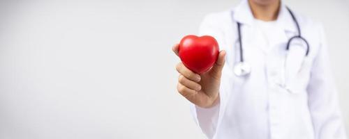 mano ravvicinata di un medico che tiene un cuore rosso per malattie cardiache, concetto di servizio di assicurazione sanitaria foto