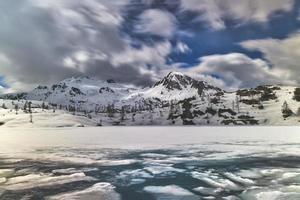 blocchi di ghiaccio nel lago alpino durante il disgelo foto