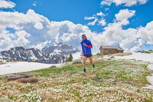 atleta corridore tra i fiori di croco dopo lo scioglimento della neve foto