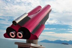 sito rosso che vede il telescopio rivolto verso l'alto su cielo nuvoloso blu e mare con sfondo di yacht yacht foto