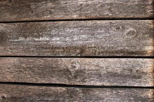 fondo della superficie del tavolo in legno scuro con struttura in legno e spazi tra le assi foto