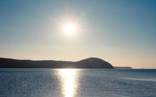 paesaggio marino con vista sulla costa e sul sole foto