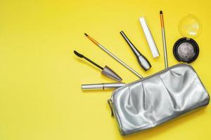 borsa cosmetica lucida grigia su sfondo giallo foto