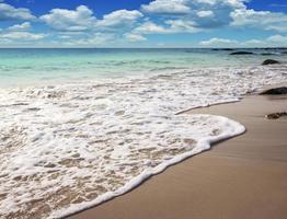 onda del mare sulla spiaggia di sabbia e cielo blu foto