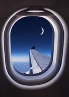 finestrino dell'aereo con la vista dell'ala e del cielo notturno foto