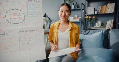 giovane asia signora insegnante di inglese videoconferenza guardando la telecamera parla dalla webcam impara insegna nella chat online a casa foto