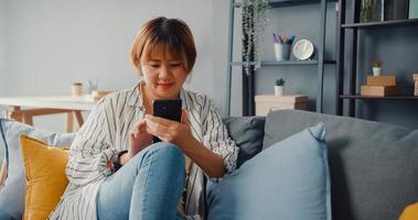 giovane signora asiatica che utilizza un messaggio di testo dello smartphone o controlla i social media sul divano nel soggiorno di casa foto