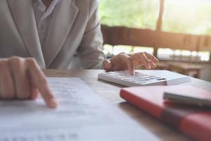 uomo d'affari che utilizza la calcolatrice per calcolare il budget e i documenti di prestito in ufficio foto