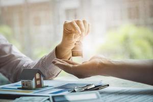 gli agenti immobiliari accettano di acquistare una casa e consegnare le chiavi ai clienti foto