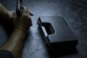 mani dell'uomo con arma e valigia da sotto la pistola sul tavolo di cemento foto