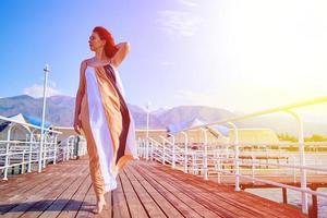 ragazza dai capelli rossi in posa con un vestito svolazzante sul molo foto