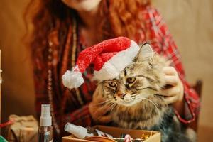 ragazza in pigiama scozzese tiene un gatto soffice con un cappello di babbo natale foto