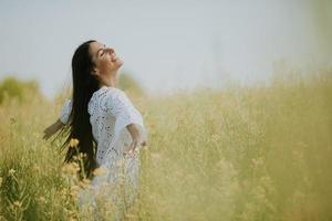 giovane donna nel campo di colza foto
