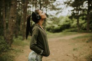 giovane corridore femminile bello ascoltare musica e fare una pausa dopo aver fatto jogging in una foresta foto