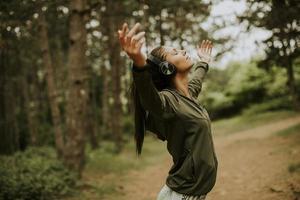 giovane donna con gli auricolari che predica le braccia nella foresta perché le piace allenarsi fuori foto