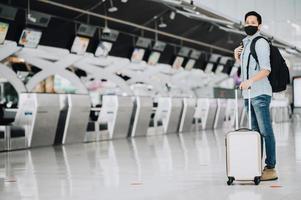 viaggiatore asiatico che indossa una maschera per proteggersi dal coronavirus in piedi con i bagagli foto