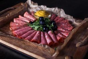 salsiccia tagliata con erbe e salsa su un vassoio di legno, bella porzione, sfondo scuro foto