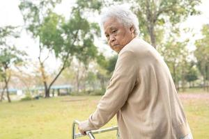 asiatica anziana o anziana donna anziana paziente cammina con deambulatore nel parco con spazio copia foto