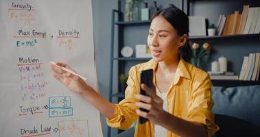 giovane insegnante asiatica in videoconferenza che chiama su smartphone parla tramite webcam impara insegna nella chat online a casa foto