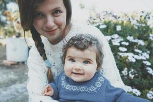 giovane mamma che abbraccia il suo bambino e godersi una giornata di primavera in giardino foto