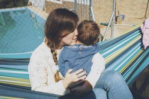 immagine sulla vera maternità di una giovane mamma che abbraccia il suo bambino foto