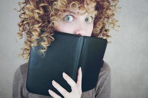 primo piano ritratto di una bella e giovane donna divertente con gli occhi azzurri e capelli biondi ricci dietro un'agenda o un ebook e lei è sorpresa foto