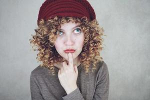 ritratto ravvicinato di una bella e giovane donna divertente e premurosa con gli occhi azzurri e i capelli biondi ricci che pensa e indossa un berretto di lana rosso foto