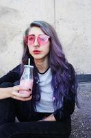 felice bella adolescente con occhiali da sole rosa beve e gode di una bevanda rosa seduto su un terreno urbano foto