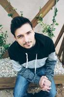 un giovane uomo attraente che guarda curiosamente la telecamera seduto su una panchina con piante dietro di lui e all'aperto foto