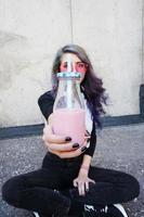 felice bella adolescente con occhiali da sole rosa esulta e si gode una bevanda rosa seduta su un terreno urbano foto