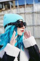 Ritratto di una giovane donna punk o gotica con capelli colorati di blu e indossando occhiali steampunk neri e berretto di lana blu in una strada urbana all'aperto foto