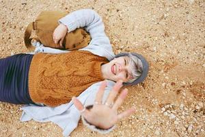 Un avventuriero giovane donna caucasica sdraiato su un terreno di sabbia accanto a uno zaino che indossa un maglione di lana e berretto con la mano aperta e l'arancione come colore principale foto