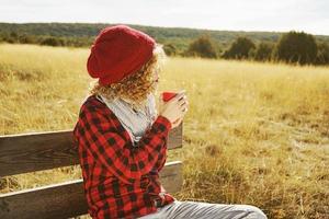 una giovane donna da dietro in camicia a quadri rossa con un berretto di lana e sciarpa che prende una tazza di tè o caffè mentre sta prendendo il sole seduta su una panca di legno in un campo giallo con retroilluminazione dal sole autunnale foto