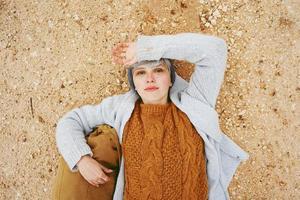 un avventuriero giovane donna caucasica sdraiato su un terreno di sabbia accanto a uno zaino che indossa un maglione di lana e un berretto di lana grigio con l'arancione come colore principale foto