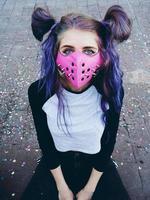giovane donna punk che indossa una maschera rosa foto