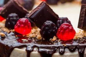 bella torta festiva con glassa al cioccolato e marmellata su uno sfondo di fiori foto