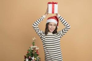 bella ragazza di natale in cappello di babbo natale con scatole su sfondo autunnale foto