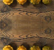 varietà di zucche su uno sfondo di legno. concetto di raccolto piatto disteso con spazio di copia. foto