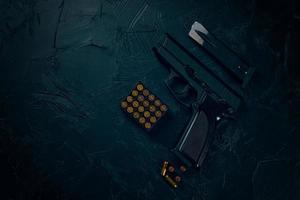 pistola e proiettili sul tavolo di cemento. foto