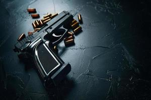 pistola con cartucce sul tavolo di cemento scuro. foto