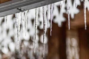 un grande ghiacciolo trasparente pende dal tetto della casa. gelate invernali foto