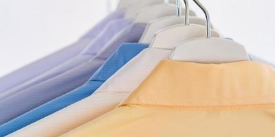 camicie da uomo, vestiti appesi su sfondo bianco foto
