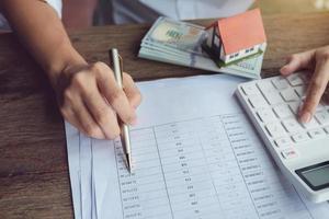 i clienti utilizzano penne e calcolatrici per calcolare i prestiti per l'acquisto della casa in base ai documenti di prestito ricevuti dalla banca foto