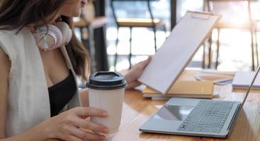 donna d'affari che tiene tazza di caffè e documenti al bar foto