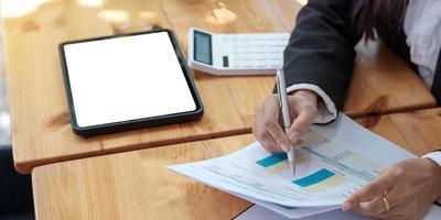 primo piano del consulente per gli investimenti della donna d'affari che analizza la dichiarazione di bilancio della relazione finanziaria annuale dell'azienda che lavora con i grafici dei documenti. immagine concettuale dell'economia, del marketing foto