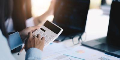 gruppo di uomini d'affari che utilizzano una calcolatrice per aumentare la produttività foto