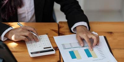 donna d'affari che utilizza calcolatrice e laptop per fare finanza matematica sulla scrivania di legno in ufficio e lavoro aziendale, tasse, contabilità, statistiche e concetto di ricerca analitica foto