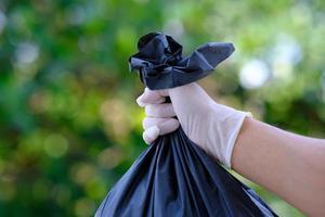 mano che tiene il sacco della spazzatura su sfondo verde bokeh e salva il mondo e ricicla il concetto foto