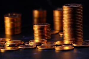 pila di monete su sfondo nero foto