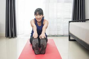 bella giovane donna sportiva che si estende a casa foto